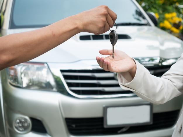 Sluit omhoog van het overhandigen van de sleutels voor een auto aan een jonge zakenman. autorijden, reizen, auto huurauto, veiligheidsverzekering Premium Foto