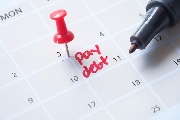 Sluit omhoog van het woord van de loonschuld op kalender Premium Foto