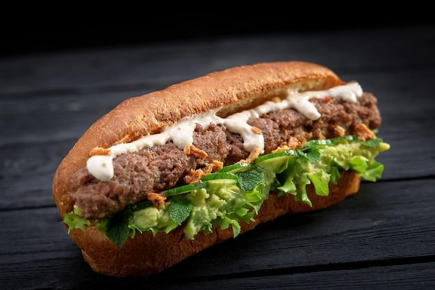 Sluit omhoog van kebabsandwich op zwarte houten achtergrond Premium Foto