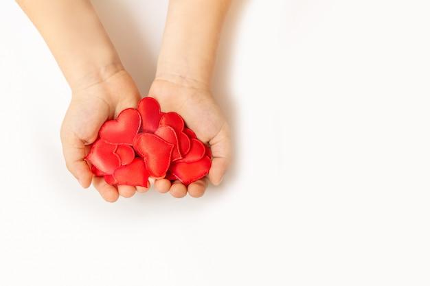 Sluit omhoog van kindhanden houdend rood hart op witte achtergrond - mensen, liefde, liefdadigheid en familieconcept Premium Foto