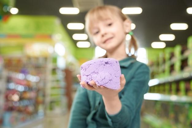 Sluit omhoog van kinetisch zand op hand van kind. Gratis Foto