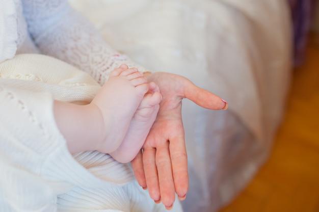 Sluit omhoog van kleine babyvoeten met moederhand Premium Foto