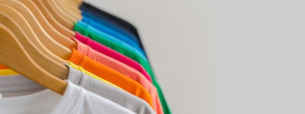 Sluit omhoog van kleurrijke t-shirts op hangers, kledingsachtergrond Premium Foto