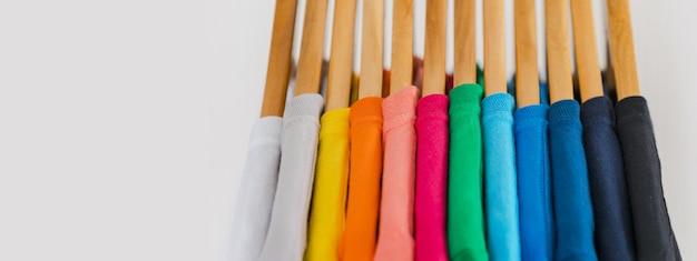 Sluit omhoog van kleurrijke t-shirts op hangers Premium Foto