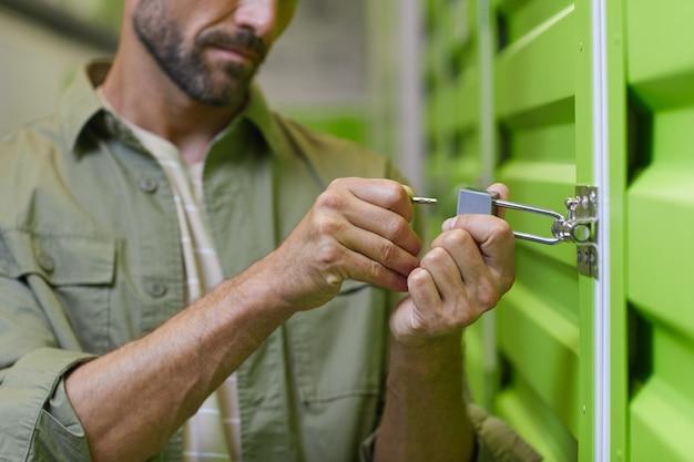Sluit omhoog van knappe mens die hangslot op deur van zelfopslageenheid openen, exemplaarruimte Premium Foto