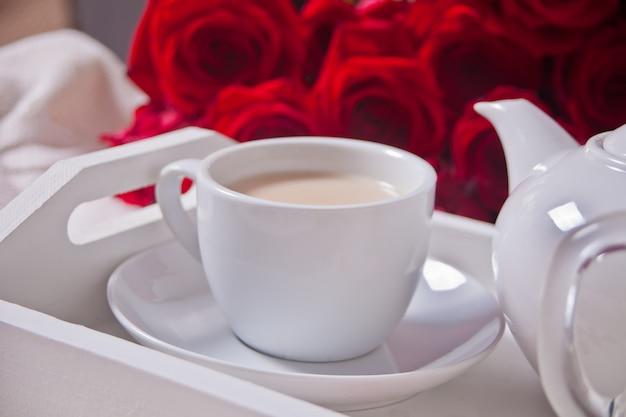 Sluit omhoog van kop thee met rode rozen op het witte dienblad Premium Foto