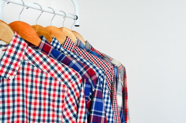 Sluit omhoog van lang koker rood en blauw geruit overhemd op houten hanger over wit Premium Foto