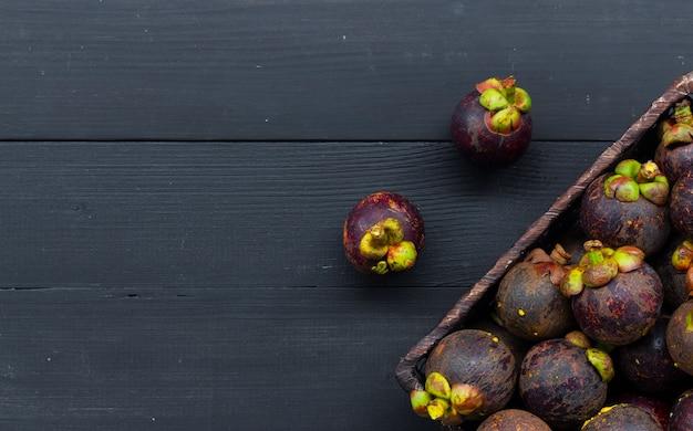 Sluit omhoog van mangostanfruit op zwarte houten lijst Premium Foto