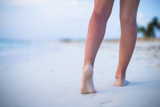 Sluit omhoog van mannelijke benen op wit zandig strand Premium Foto
