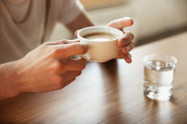 Sluit omhoog van mannelijke handen houdend kop van koffie, onderwijs en bedrijfsconcept Gratis Foto