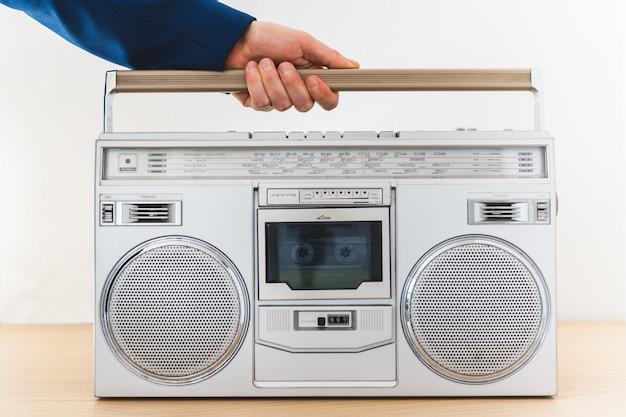 Sluit omhoog van mensenhand houdend een oude radio binnen. Premium Foto
