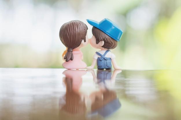 Sluit omhoog van minipaarpoppen in romantische kus voor de dagconcept van valentine Premium Foto