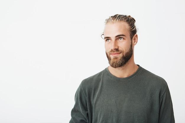 Sluit omhoog van mooie mannelijke kerel met licht haar, modieus haar en baard in grijs overhemd die en opzij met prettige uitdrukking glimlachen kijken. Gratis Foto