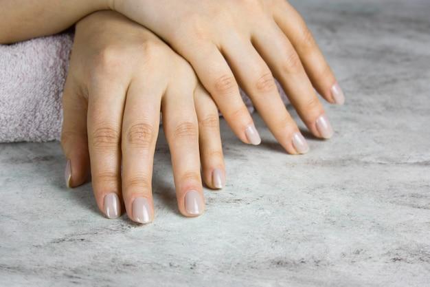 Sluit omhoog van mooie vrouwelijke handen met manicure op marmeren lijst Premium Foto