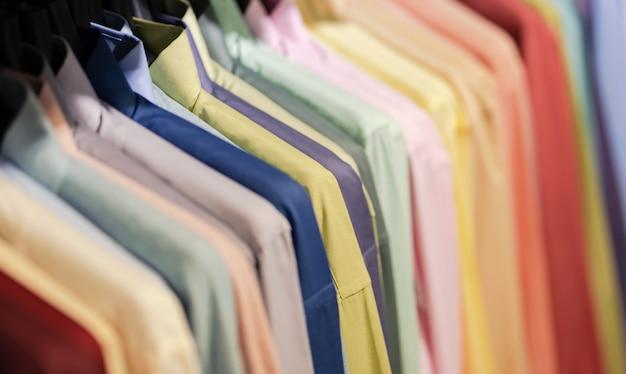 Sluit omhoog van multi gekleurde overhemden op hangers, de kleurrijke achtergrond van de kledingsdoek Premium Foto