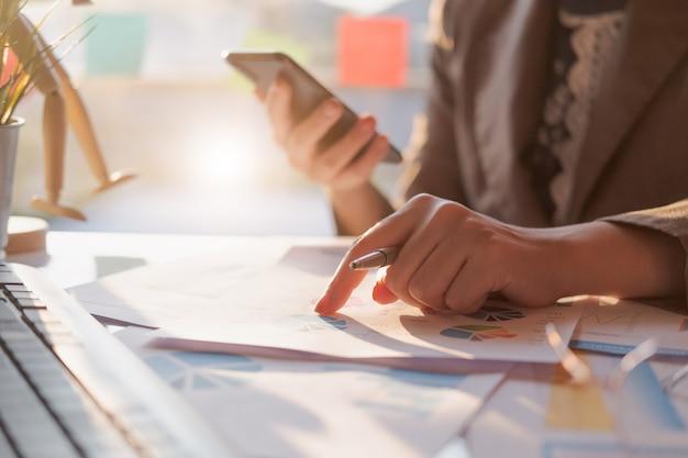 Sluit omhoog van onderneemster of het potlood die van de accountantshand aan het slimme rapport van telefoongegevens, boekhoudingsdocument en laptop computer op kantoor, bedrijfsconcept werken Premium Foto