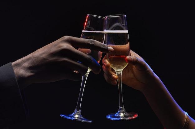 Sluit omhoog van onherkenbaar afrikaans-amerikaans paar rammelende champagneglazen in donkere, exemplaarruimte Premium Foto