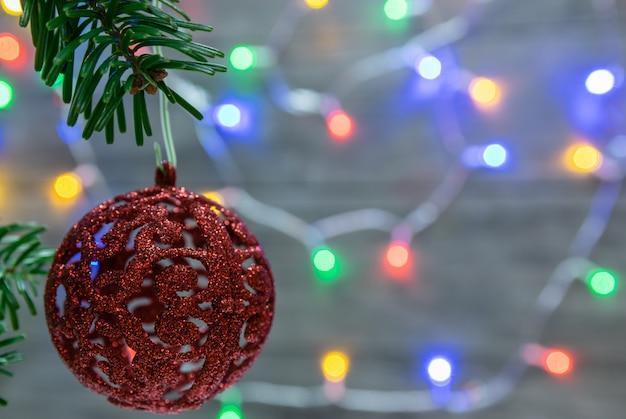 Sluit omhoog van ornamenten op een takjekerstboom en achtergrond met kleurrijke lichten Premium Foto