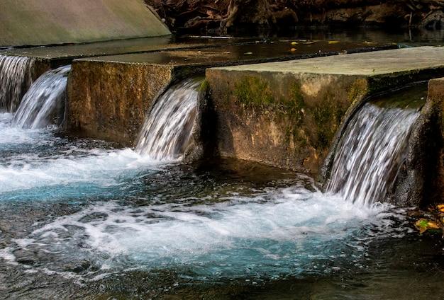 Sluit omhoog van oud concreet afvoerkanaal in rivier bij het tropische bos. Premium Foto