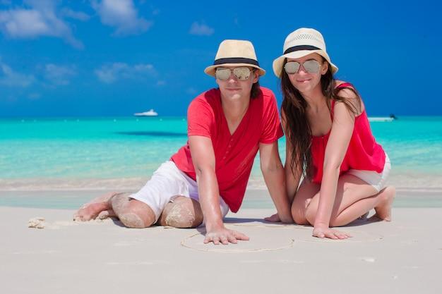 Sluit omhoog van paarzitting in het hart op tropisch wit strand Premium Foto