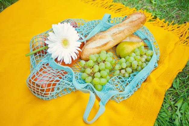 Sluit omhoog van picknickzak met voedsel, vruchten en bloem op de gele dekking op het groene gras Premium Foto
