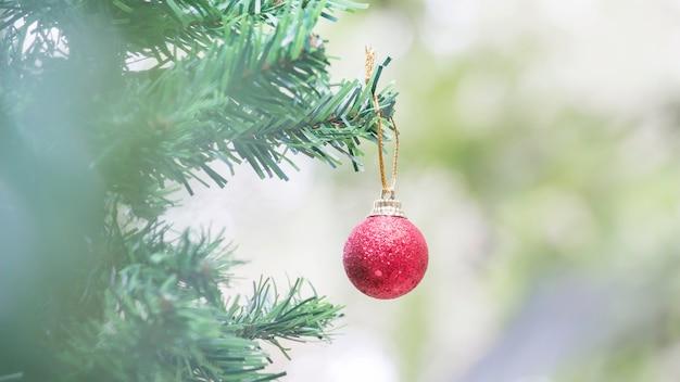 Sluit omhoog van rode bal en pinecone voor kerstmis op vage lichten Premium Foto