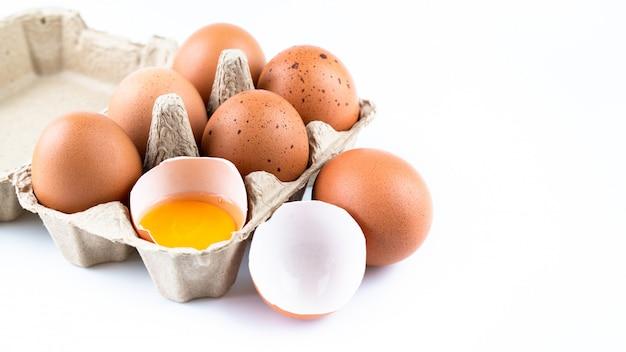 Sluit omhoog van ruwe kippeneieren in geïsoleerde eidoos en shell Premium Foto