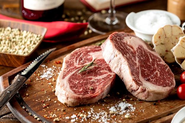 Sluit omhoog van ruwe lapje vleesstukken die met zout en kruiden worden versierd Gratis Foto
