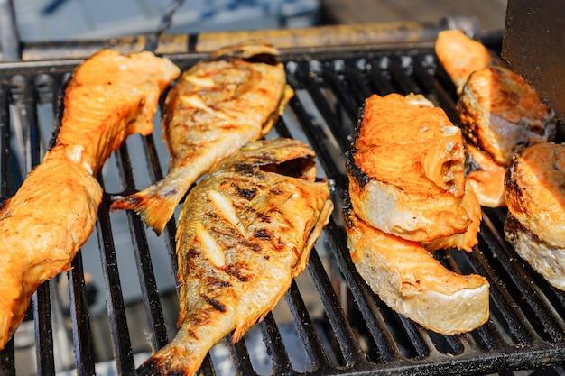 Sluit omhoog van smakelijke geroosterde zalm en toppositie bij de grill in openlucht. straatvoedsel. Premium Foto