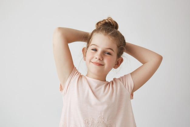 Sluit omhoog van snoepje weinig blondemeisje met broodjeskapsel in het roze t-shirt glimlachen, houdend handen achter hoofd met gelukkige en tevreden uitdrukking. Gratis Foto