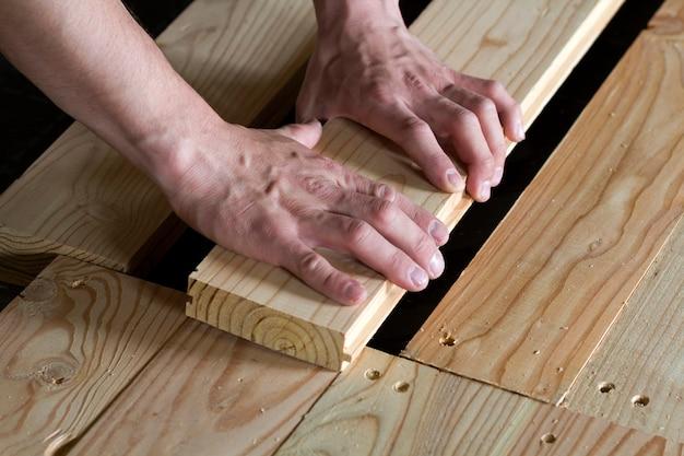 Sluit omhoog van sterke spierhanden van professionele timmerman die natuurlijke houten nieuwe planken installeren op houten frame wederopbouw, verbetering, vernieuwings en timmerwerkconcept. Premium Foto