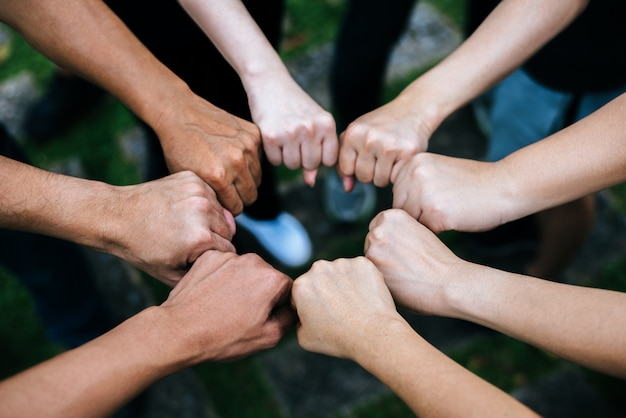 Sluit omhoog van studenten die handen bevinden die vuistbuilgebaar maken. Gratis Foto