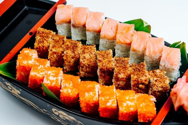 Sluit omhoog van sushi met hete en koude broodjes worden geplaatst dat Gratis Foto