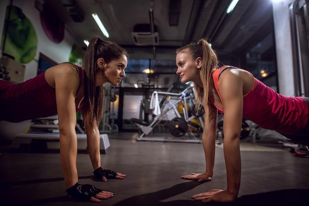 Sluit omhoog van twee knappe slanke atletische geschiktheidsvrouwen die opdrukoefeningen samen voor elkaar doen en elkaar in de gymnastiek kijken. Premium Foto