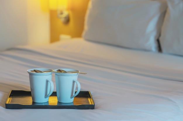 Sluit omhoog van tweeling welkome koffiekop op wit bed in hotelruimte - het concept van de de vakantiereis van de hotelkoffie Gratis Foto