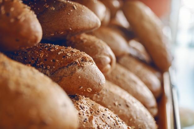 Sluit omhoog van vers gebakken broodje schort klaar te eten op. bakhuis interieur. Premium Foto