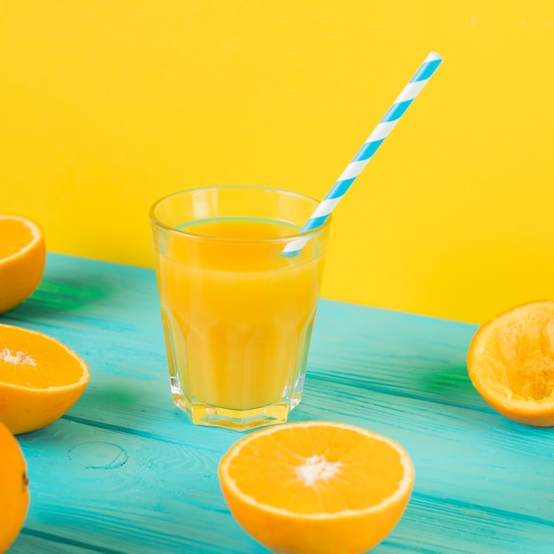 Sluit omhoog van vers jus d'orangeglas op blauwe lijst Gratis Foto