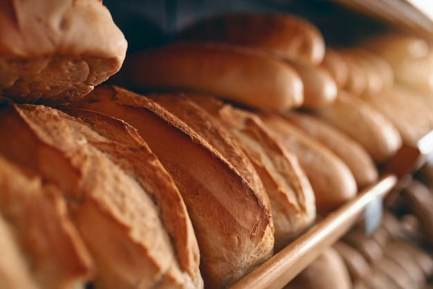 Sluit omhoog van verse heerlijke broden in rij op planken klaar voor verkoop. bakkerij interieur. Premium Foto