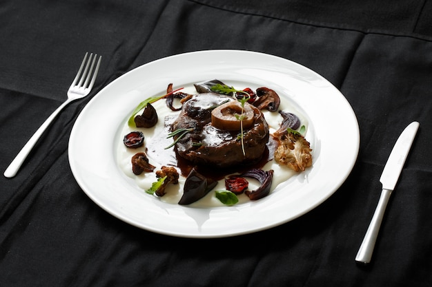 Sluit omhoog van vleesschotel met geroosterde groenten Premium Foto