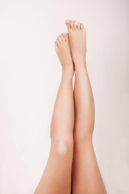 Sluit omhoog van vrouw die massage voor haar vlotte benen doet Premium Foto