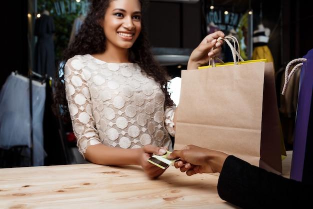 Sluit omhoog van vrouw die voor aankopen in winkelcomplex betalen Gratis Foto