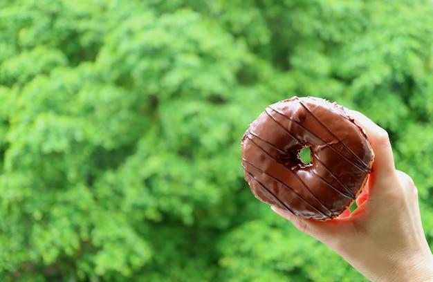 Sluit omhoog van vrouwelijke hand die een chocolade met een laag bedekte doughnut met vaag trillend groen gebladerte op achtergrond houden Premium Foto