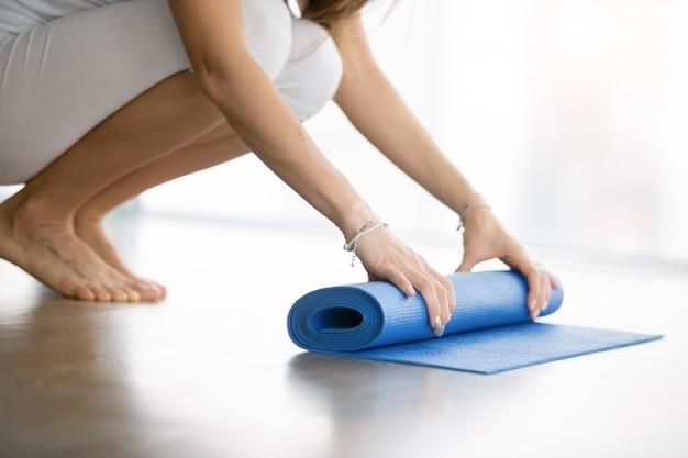 Sluit omhoog van vrouwelijke handen die yoga matress uitrollen Gratis Foto
