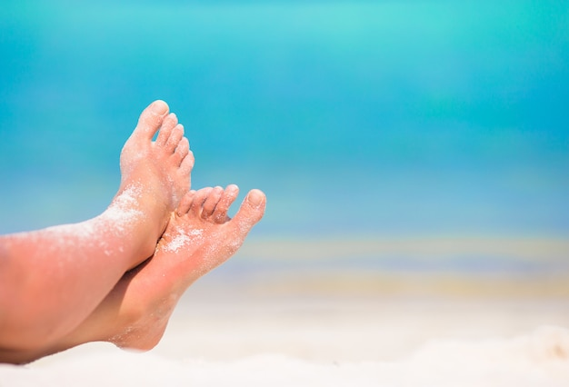 Sluit omhoog van vrouwelijke voeten op wit zandig strand Premium Foto