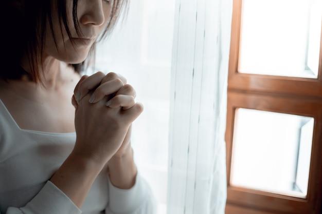 Sluit omhoog van vrouwenhanden die bij kerk bidden, vrouw geloven en bidden tot god. Premium Foto