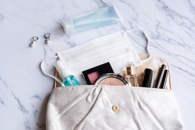 Sluit omhoog van vrouwentoebehoren, ontsmettingsmiddel, alcoholnevel en beschermend gezichtsmasker op zak, schoonheidsconcept. plat liggen Premium Foto