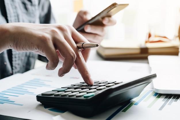 Sluit omhoog van zakenman of accountant de pen die van de handholding aan calculator werken om bedrijfsgegevens te berekenen Premium Foto