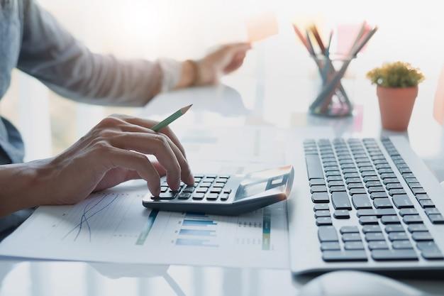 Sluit omhoog van zakenman of accountantshand houdend potlood die aan calculator werken om financieel gegevensrapport, boekhoudingsdocument en laptop computer op kantoor, bedrijfsconcept te berekenen Premium Foto