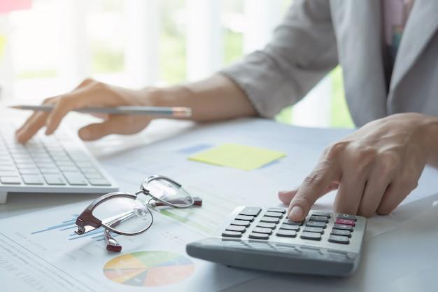 Sluit omhoog van zakenman of de holdingspen die van de accountanthand aan calculator werken Premium Foto