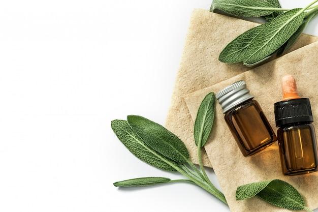 Sluit omhoog vers groen wijs kruidblad met een fles etherische olie op witte achtergrond, kruidessentie Premium Foto